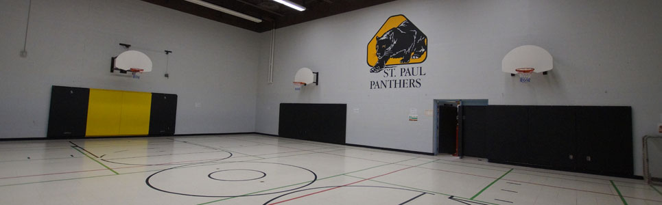 St. Paul Catholic School gym, their logo of a black panther painted on the wall above basketball nets.