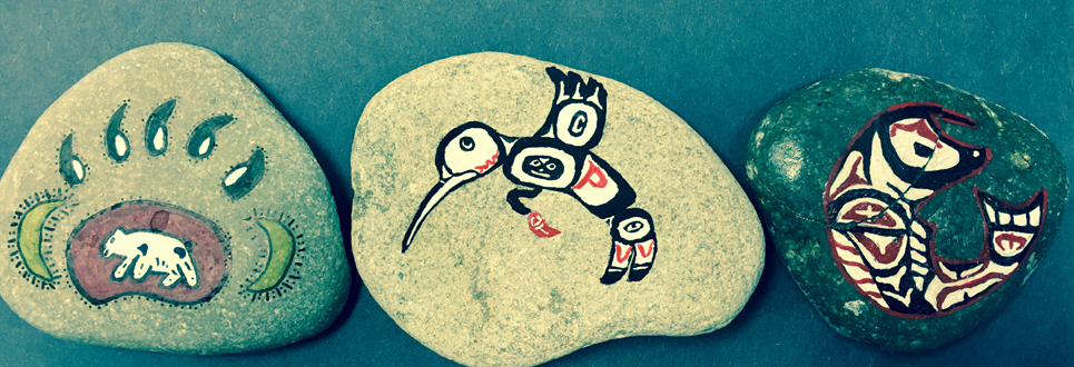 Hand painted rocks illustrating animals and symbols highlighting our Indigenous people